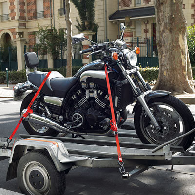 Motorcycle on trailer secured by a tie down strap
