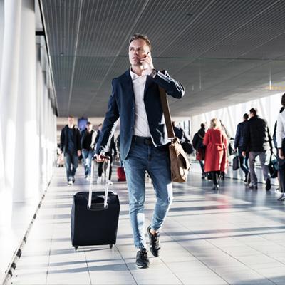 Mann mit Handgepäck und Handy am Flughafen